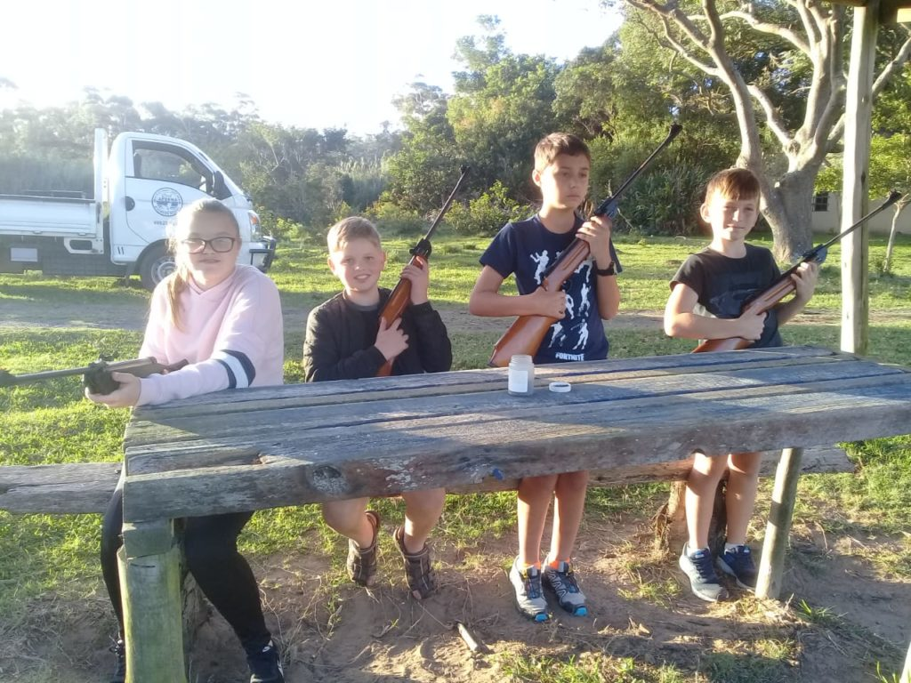 4 children holding pellet guns waiting to take aim