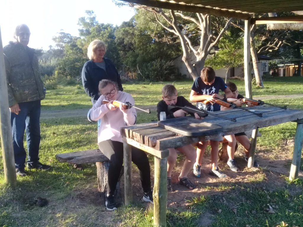 4 Children aiming pellet guns for pellet gun target shooting, with parents watching