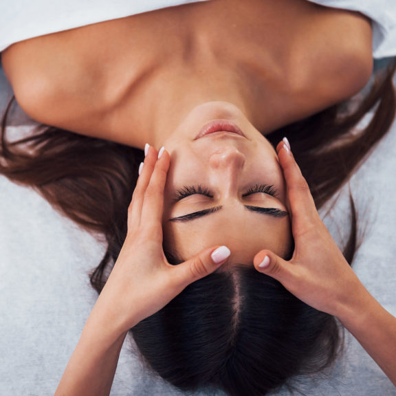 Close up view of woman that lying down in spa salon and have face massage